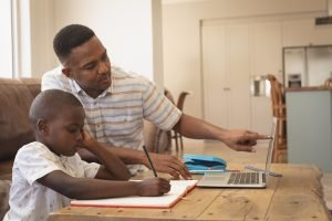 African American father helping his son with homework on laptop at table (Featured Image: Trauma-Informed Practices Across School Settings)