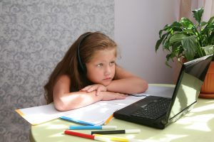 Featured Image (Webinar): Student Mental Health in a Distance Learning Environment - Focused child in self isolation wearing headphones looking at a laptop